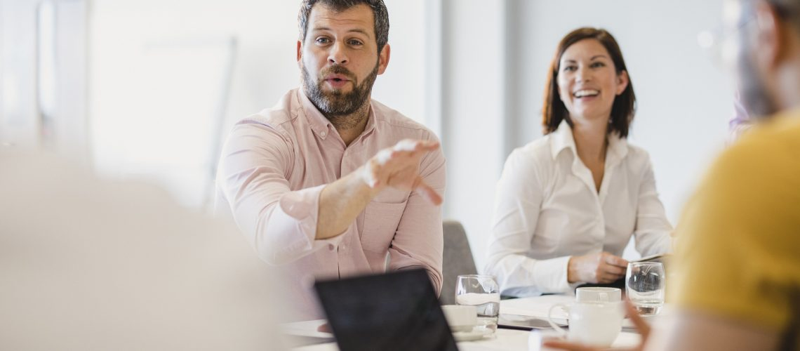 Mature man in his 40s gesturing and talking, sitting at meeting table in board room, discussion, collaboration, strategy